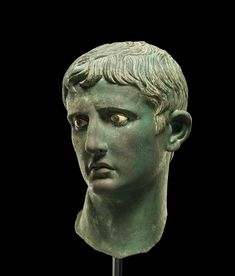Bronze head from an over-life-sized statue of Augustus: the head is broken through the neck but is otherwise in an excellent state of preservation.  There are four fragments of plaster from the head. The eyes are inlaid, with glass pupils set in metal rings, the irises of calcite. The eyebrows are plastically rendered. The emperor's head is turned to his right, with the pronounced twist to the neck typical of Hellenistic work. The hair falls on the brow in the divided and curving cut that…