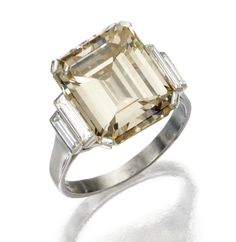 PLATINUM AND FANCY YELLOW-BROWN DIAMOND RING, BULGARI, FRENCH.  The emerald-cut diamond of fancy yellow-brown color weighing 8.59 carats, flanked by near colorless baguette diamonds, size 6¾, signed Bulgari, maker's mark, French assay mark.