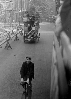 1890's London with a cyclist in the foreground and an omnibus, probably horse-drawn, in the background.