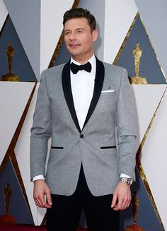 Ryan Seacrest dressed in a nice gray suit with black details