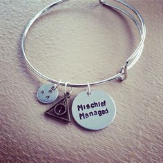 "Mischief Managed Deathly Hallows Adjustable Bangle Bracelet Handmade Harry Potter Inspired  A handmade and hand stamped bracelet, with  ""mischief managed"" written across the 3/4"" disc, a deathly hallows charm, and book page star charm. This bangle is adjustable, similar to Alex & Ani style brac..."
