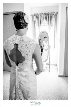 Bride looking at herself in the mirror before wedding in Seville, Ohio.