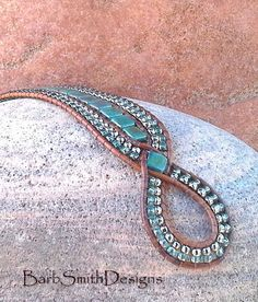 The Diamond Princess in Bronzed Teal  The Diamond Princess is a slimmer version of my Queen of Diamonds. The Princess was designed with a focal point of (2) two diamonds of Bronzed Picasso Teal Czech glass tile beads, entwined in a weave of distressed-finish Light Brown Indian leather cord. It is hand-stitched in tile beads, surrounded by (4) four rows of Nickel Oxide and Celsian Blue seed beads. The front closure is a 5/8 antique silver flower button with a beaded button loop.  Finished…