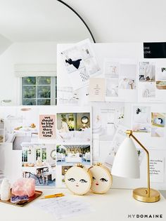 Home office with a white desk, a gold and white task lamp, and a large mood board