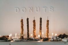 Dessert Bar: Towering columns of donuts are as clean and crisp as the modern white signage behind them. Simple white candles cast a soft glow that shine a spotlight in these sweet desserts.