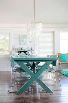 Kronleuchter in Weiß über einem Esstisch aus Holz in der Farbe Türkis