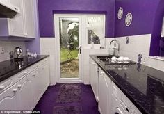 Fifty shades of purple: The white kitchen unit is offset by the purple walls and carpet