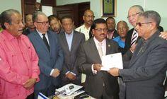 Junior Santos entrega la incripción de la candidatura de Neney Cabrera, a don Pedro Reynoso, al fondo se observa a Alex Aquino. FOTO: Sanchito Sánchez