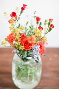 orange and yellow flowers in a mason jar vase - Photo by Petra Veikkola