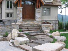 Escaliers chaleureux mettant en valeur l'avant de la maison de manière naturelle et minérale. Une réalisation d'aménagement paysager au Québec par Maxhorti. #Landscaping