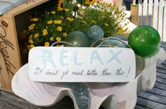 """Here is a very beach/cottage style sign, rustic white & blue coastal color. Sign has been carved saying """"RELAX, It just doesn't get better than this"""". 14 inches long."""