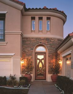 A mahogany JELD-WEN custom fiberglass door adds an artistic touch to this home's entry.