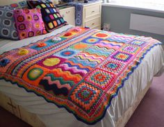 Amazing crocheted blanket in a rainbow of colours: pink (lots), red, turquoise, purple, yellow, orange...