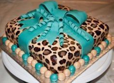 Cute leopard print birthday cake wrapped in edible turquoise ribbon.
