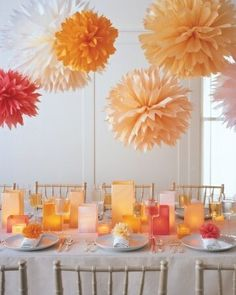 entertaining wedding birthday dinner party table setting decorations peach orange coloured paper pom poms, wooden tiffany chairs, cream white linen napery