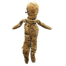 Roman, 1st-5th century AD Made in Egypt A linen doll, filled with rags and papyrus This doll is fairly well-proportioned, and has a head and a body. The arms are made from a long roll of linen attached at the back. The doll is made of made of coarse linen and is stuffed with rags and pieces of papyrus. Coloured wool, now faded, was applied to parts of the face and body.