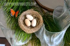 Adding nests, eggs, and butterflies transitions the pine wreath from winter to spring.
