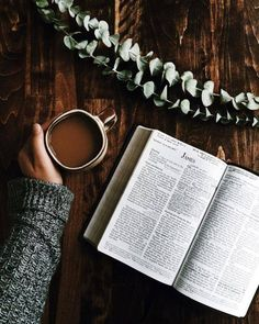 Hand with a cup of coffee and open bible