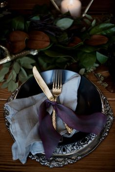 a moody place setting with a greenery table runner, dark plates and a silver charger