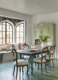 An aged-to-perfection dining table in a vivid aqua hue and a stunning sage cupboard give the dining room shabby chic charm. A window bench is piled high with bold pillows for a pop of color and added comfort.