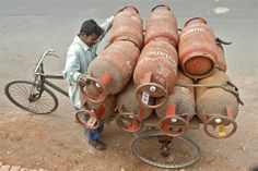 A worker loads Liquefied Petroleum Gas (LPG) cylinders onto his cycle-rickshaw in Kolkata, India. (Reuters)
