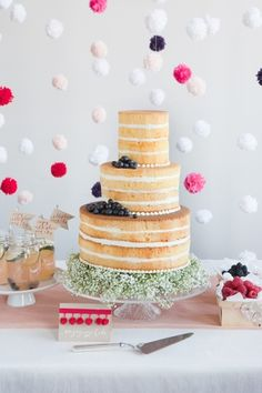 Naked cake with fresh blueberries and a base of baby's breath. Originally published in Seattle Met Bride & Groom magazine. Cake by Honey Crumb Cake Studio, www.honeycrumb.com. Image © Clare Barboza Photography.