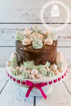 3 layers of vanilla sponge and vanilla buttercream, a smoosh of milk chocolate ganache and topped off with homemade meringue kisses...follow me at www.facebook.com/Cakes.at.Rachels for more yummy delights!