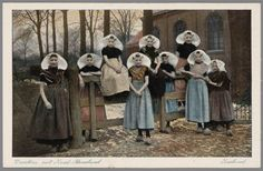 Groep meisjes in protestantse Zuid-Bevelandse streekdracht. De meisjes dragen doordeweekse dracht, met klompen. Enkele van hen hebben tegen de koude een omslagdoek omgeslagen. na 1905 #Zeeland #ZuidBeveland #protestant