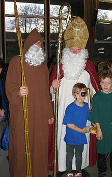 Knecht Ruprecht, which translates as Farmhand Rupert or Servant Rupert, is a companion of Saint Nicholas as described in the folklore of Germany. He first appears in written sources in the 17th century, as a figure in a Nuremberg Christmas procession.  Tradition holds that he appears in homes on St. Nicholas day (December 6), and is a man with a long beard, wearing fur or covered in pea-straw. Knecht Ruprecht sometimes carries a long staff and a bag of ashes, and wears little bells on his