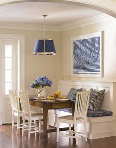 Nice cozy eating area. Like the creamy yellow walls and blue accents.  Natural wood table adds warmth.