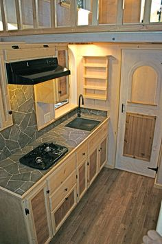In the kitchen is custom built birch cabinetry, a 4.5 cu.ft. refrigerator, and an Atwood two burner gas cooktop.