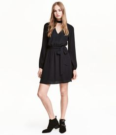 Black. Short dress in woven fabric. Small stand-up collar, cut-out sections at front and back, long sleeves, and buttons at back of neck. Elasticized seam