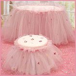 Layers of tulle sprinkled with flower petals, decorate both the vanity table and cushioned stool.
