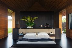 Wide open natural wood bedroom with potted plants and white bedding.