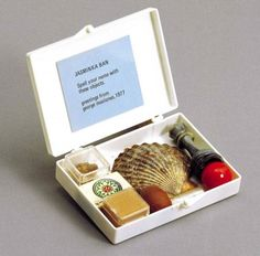 """George Maciunas SPELL YOUR NAME WITH THESE OBJECTS. 1977 White plastic box with label containing different objects assembled by the artist. 7 x 9.4 x 2.2 cm. Described in the letter sent from Rosanna Chiessi to G. Politi and published in the magazine """"Flash Art"""", 1978"""