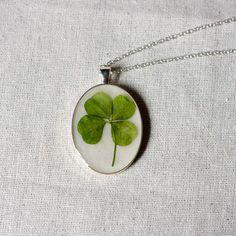 four leaf clover real pressed leaf botanical pendant. sage green 4 leaf clover set in resin get lucky luck saint patricks day. $45.00, via Etsy.