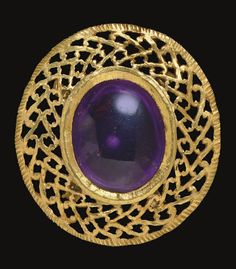 A ROMAN GOLD AND AMETHYST BROOCH   CIRCA 3RD-4TH CENTURY A.D.   With a convex oval cabochon amethyst set in a plain flanged bezel enclosed within a broad oval frame of pierced-work volutes, edged with a hatched border, with four wide plain hoops on the underside for attachment