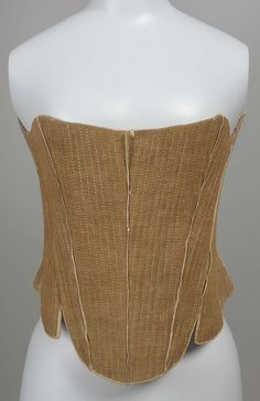 Brown stays with undyed linen lining, shallow rounded waist tabs, edged in leather, seams covered in linen tape except for two on wearer's left which are covered with narrow leather strips, undyed linen stitching through out and around seven sets of lacing holes at back, stitching goes through lining and appears on inside of stays