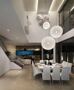 Modern spaces with an usual large square dining table and defused globe light fixtures.....beautiful space.
