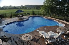 In-ground pool featuring a vinyl liner, hardscape fencing, concrete patio and deck jets. Backyard Pool Landscaping, Backyard Pool Designs, Swimming Pools Backyard, Swimming Pool Designs, Landscaping Ideas, Backyard Ideas, Vinyl Pools Inground, Cheap Pool, Outdoor Fireplace Designs