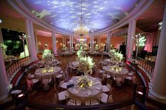 beautiful reception seating area and decor - white floral centerpieces,chandeliers, pink and purple lighting with stars on the ceiling -  photo by Houston based wedding photographer Adam Nyholt
