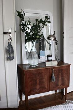 old dresser, large vase, large white mirror and ikea lamp