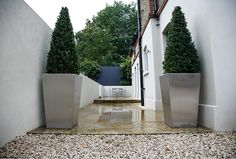 Stainless steel planters framing entrance to courtyard garden