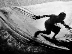 Black and white silhouette shot of a surfer on a wave