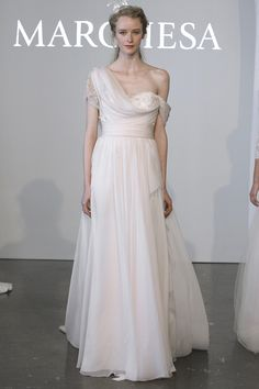 An unusual and soft take on a one shoulder gown by Marchesa. Love the blush color. The draping in top is done perfectly. An angelic dress, but with sophistication.