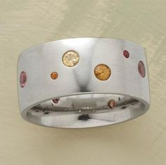 Once in a blue moon, nature produces a sapphire of uncommon hue. Anne Sportun's satin-finished 14kt white gold band is sprinkled with a dozen such rarities in pink, yellow and orange. Handmade in Canada. Whole sizes 5 to 8.