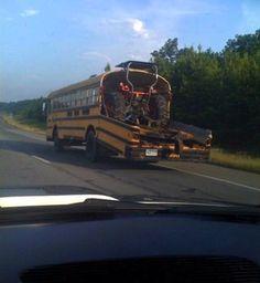 A school bus hauling a tractor.