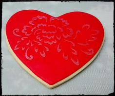 Galleta corazón rojo con decoración de rosa con stencil.  http://ditartas.com/