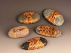 "By Del Webber: ""knotting techniques from traditional Japanese and Native American basketry, wicker furniture, loom weaving, fly-tying, and nautical knotting. Each stone is selected and wrapped with a unique design made of various materials including bamboo, cane, rattan, and reed."""