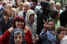 A woman makes the peace sign as people wait in the rain to cast their ballots to vote in the referendum at Escola Collaso I Gil public school polling station on October 1, 2017 in Barcelona, Spain. More than five million eligible Catalan voters are estimated to visit 2,315 polling stations today for Catalonia's referendum on independence from Spain. The Spanish government in Madrid has declared the vote illegal and undemocratic.